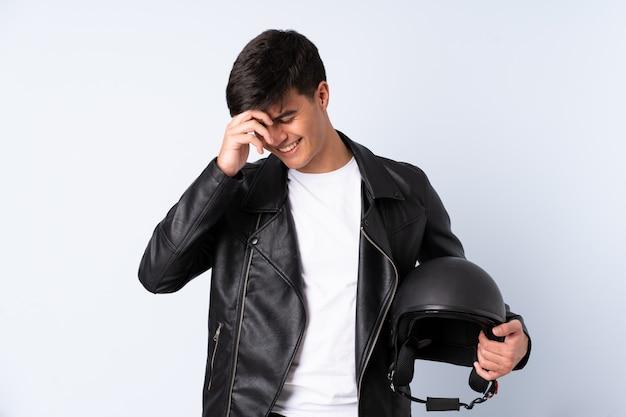 Человек с мотоциклетным шлемом на синем фоне смеется