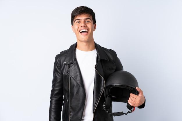 Человек с мотоциклетным шлемом на синем фоне с удивленным выражением лица