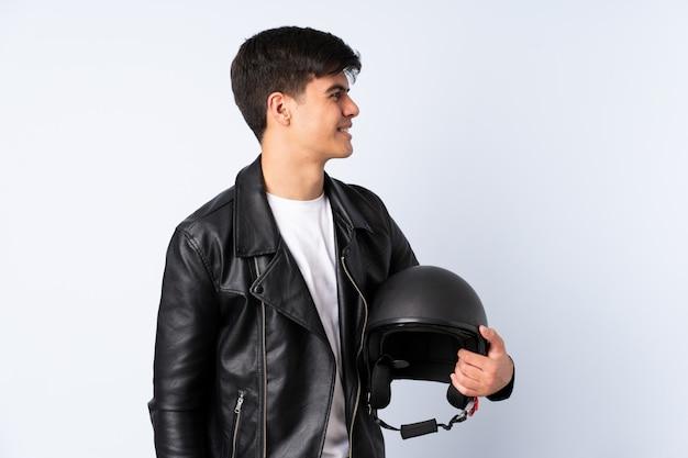 Человек с мотоциклетным шлемом над изолированным синим фоном, глядя в сторону