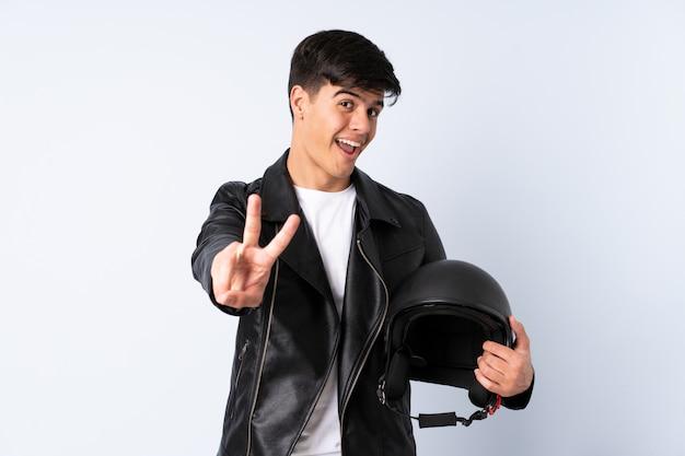 Человек с мотоциклетным шлемом на синем фоне улыбается и показывает знак победы