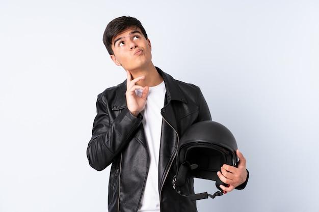 Человек с мотоциклетным шлемом над изолированной голубой предпосылкой думая идея