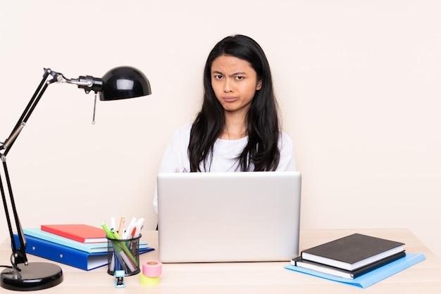ベージュ色の背景の動揺に分離されたラップトップで職場で学生アジアの女の子
