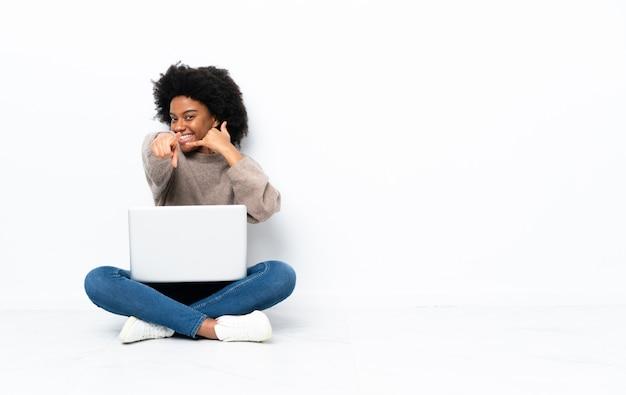 Молодая афро-американская женщина при компьтер-книжка сидя на поле делая жест телефона и указывая фронт