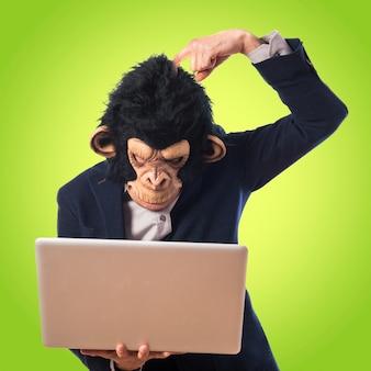 Человек-обезьяна сомневается в своем ноутбуке на цветном фоне