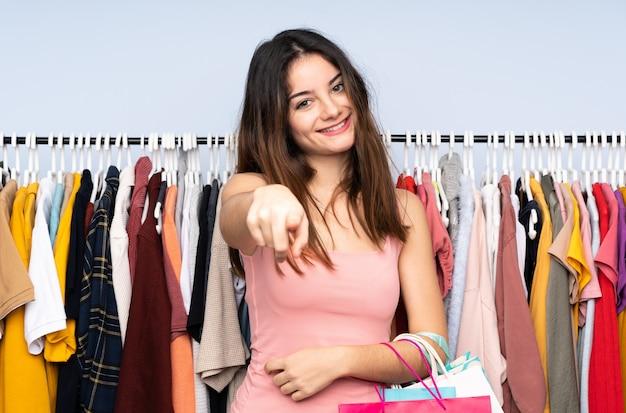 店でいくつかの服を購入する若い白人女性は自信を持ってあなたに指を指す