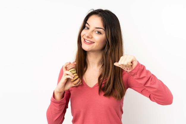 カラフルなフランスのマカロンを保持し、誇りに思っているピンクの壁に分離された若い白人女性