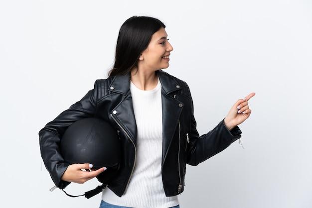 分離の白い壁にバイクのヘルメットをかざす若い女性驚いて側に指を指す