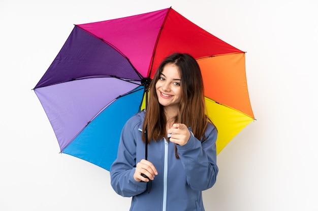 白い壁に分離された傘を保持している女性はあなたに指を指す