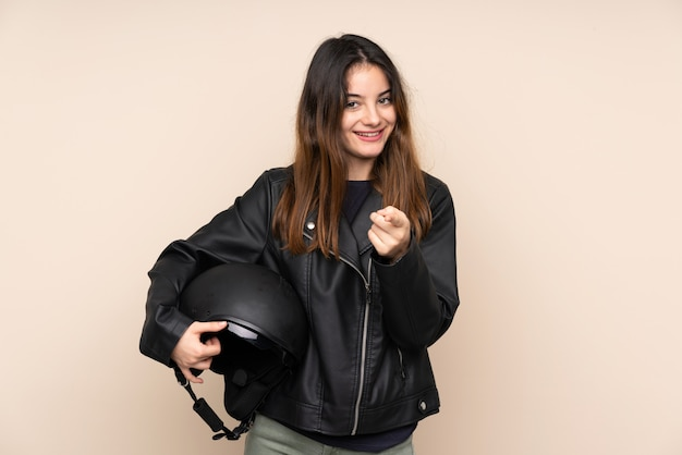 ベージュの壁に分離されたオートバイのヘルメットを持つ女性が指を指す