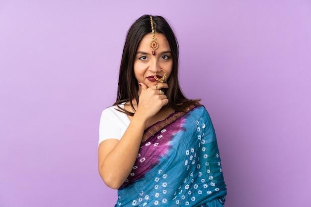 Молодая индийская женщина, изолированные на фиолетовые стены мышления