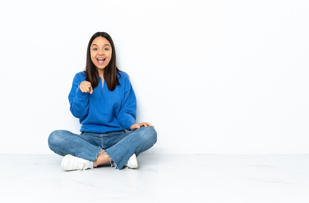 驚いて、前方を向く白い壁に分離された床に座っている若い混血女性