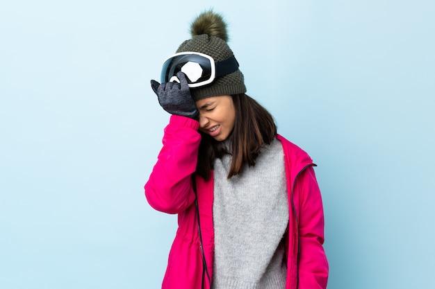 Девушка лыжника смешанной гонки с сноуборд очки над изолированных синей стеной с головной болью