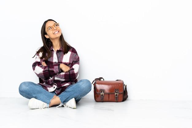 笑みを浮かべて見上げる床に座っている若い学生女性