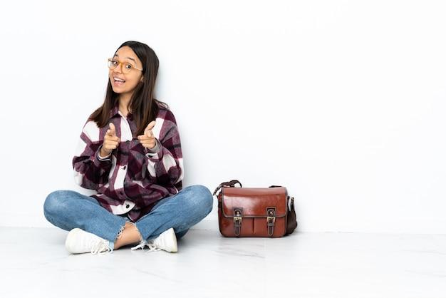 驚いて、前を指して床に座っている若い学生女性