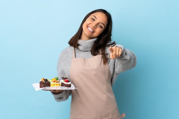 幸せそうな表情で前を指している孤立した青い壁に大きなケーキを置くパティシエ