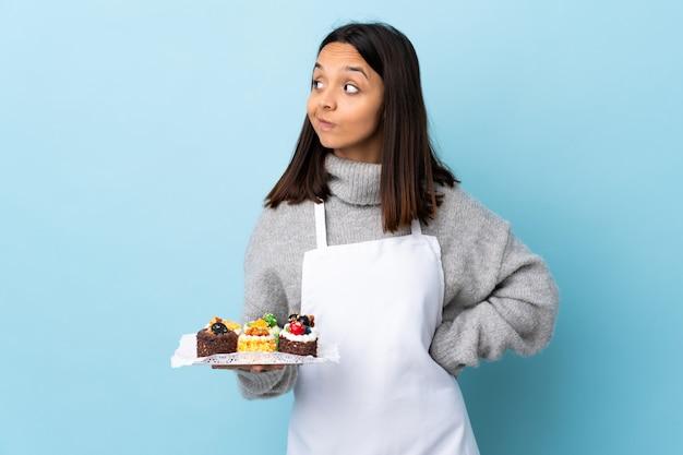 孤立した青い壁の上に大きなケーキをかざしてパティシエがジェスチャー側を疑うジェスチャー