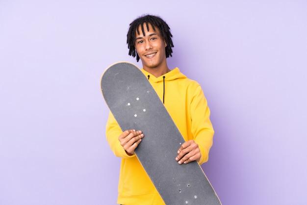 Красивый молодой скейтер человек над изолированной стеной с счастливым выражением