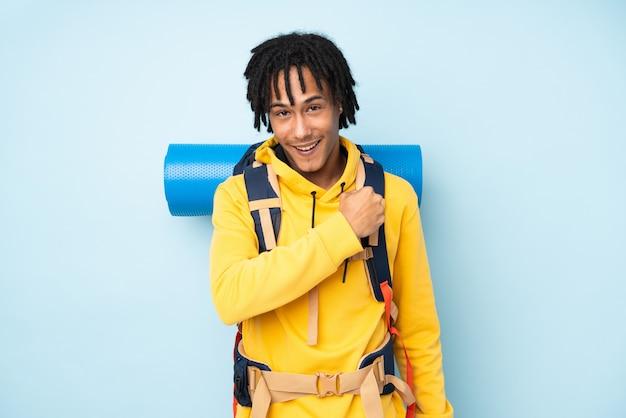 Молодой альпинист афроамериканец человек с большим рюкзаком, изолированных на синей стене, празднует победу
