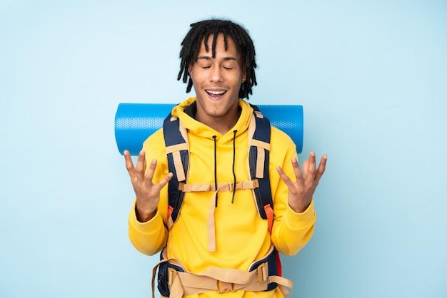 不幸な青い壁に分離されて何かに不満の大きな壁に分離された大きなバックパックを持つ若い登山家アフリカ系アメリカ人