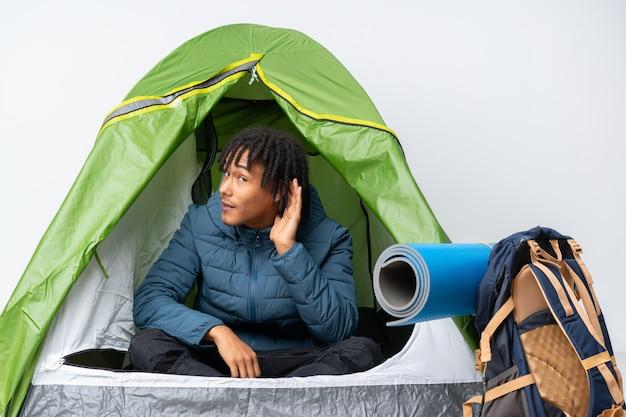 Молодой афроамериканец человек в палатке зеленый кемпинг, слушая что-то, положив руку на ухо