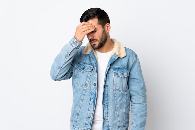頭痛で白い壁に分離されたひげの若いハンサムな男