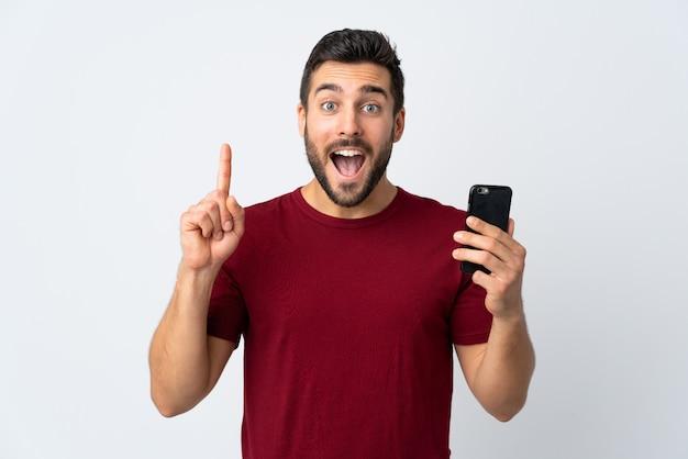 素晴らしいアイデアを指している白い壁に分離された携帯電話を使用してひげを持つ若いハンサムな男