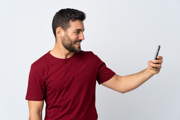 幸せな表情で白い壁に分離された携帯電話を使用してひげを持つ若いハンサムな男
