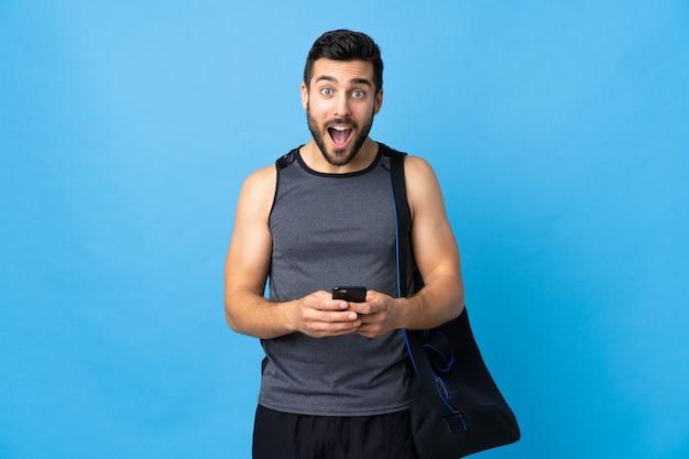 驚いて、メッセージを送信する青い壁に分離されたスポーツバッグを持つ若いスポーツ男
