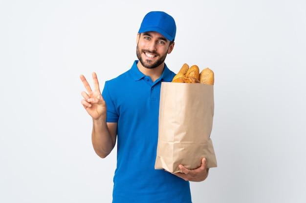 笑顔と勝利のサインを示す白い壁に分離されたパンの完全な袋を保持している配達人