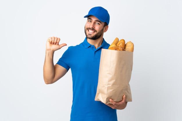 誇りと自己満足の白い壁に分離されたパンの完全な袋を保持している配達人