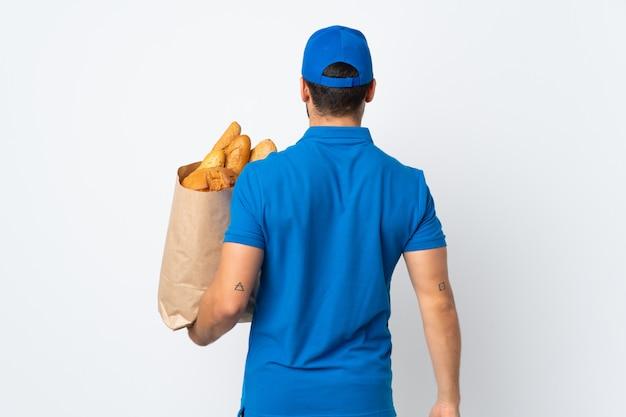 後ろの位置に白い壁に分離されたパンの完全な袋を保持している配達人