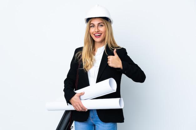 Молодая женщина архитектора с шлемом и держать светокопии над изолированной белой стеной давая жест больших пальцев руки вверх