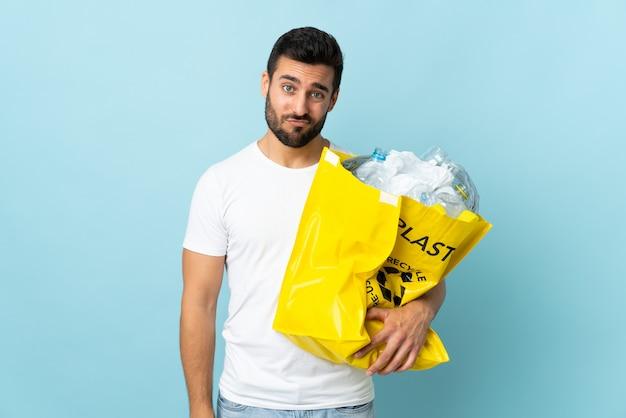 悲しい表情で青い壁に分離されたリサイクルするペットボトルの完全な袋を保持している若い白人男