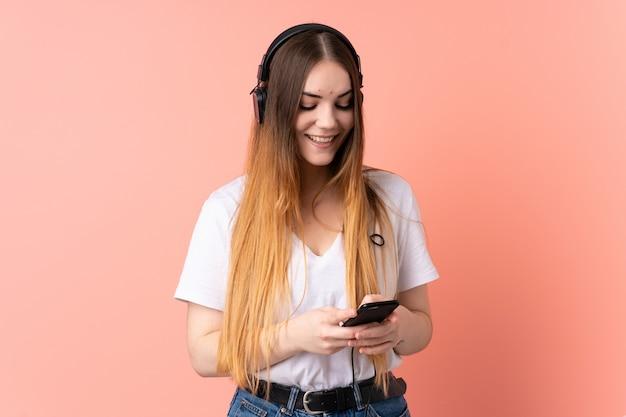 Молодая кавказская женщина изолированная на музыке розовой стены слушая и смотря к черни