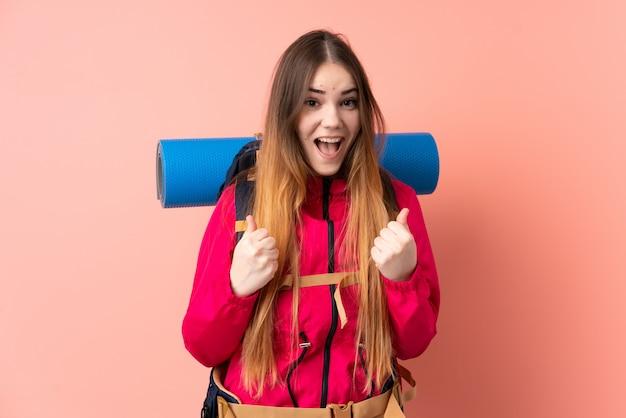 Молодая девушка альпиниста с большим рюкзаком на розовой стене празднует победу