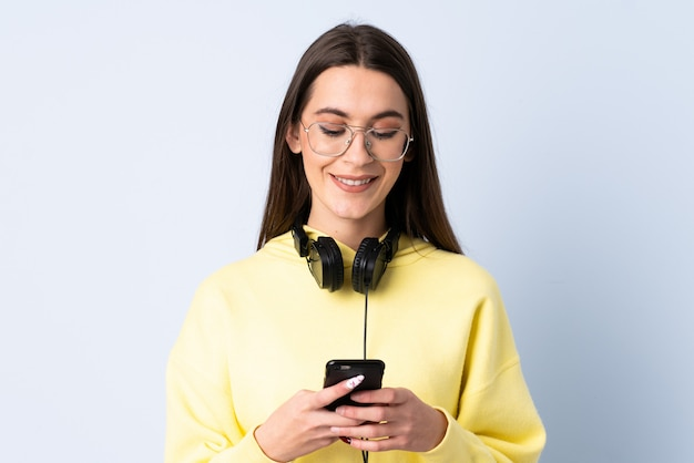 Молодая женщина над изолированной синей стеной, слушая музыку и глядя на мобильный