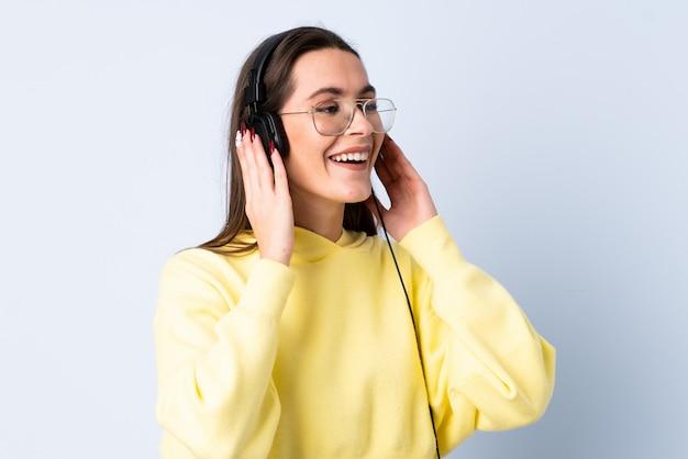 Молодая женщина над изолированной синей стеной прослушивания музыки и пения