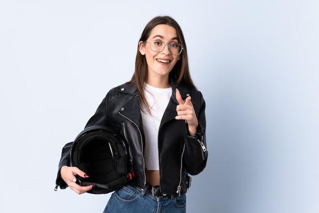 分離の青い壁にオートバイのヘルメットをかざす若い女性が指を指す