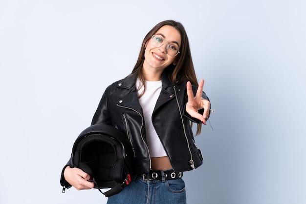 笑顔と勝利のサインを示す分離の青い壁にオートバイのヘルメットを保持している若い女性
