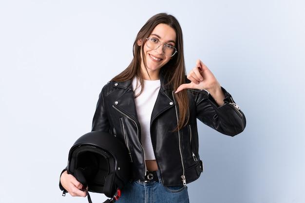 分離された青い壁に誇りと自己満足の上のオートバイのヘルメットを保持している若い女性