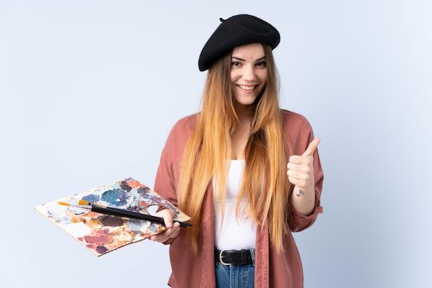 親指のジェスチャーを与える青い壁に分離されたパレットを保持している若いアーティストの女性