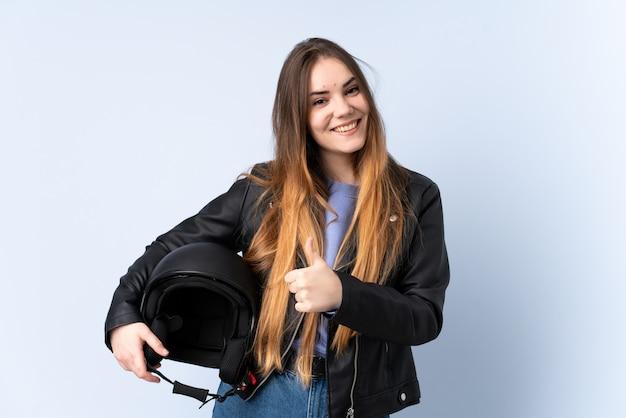 親指のジェスチャーを与えるオートバイのヘルメットを持つ女性