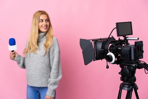 Репортер женщина, держащая микрофон и сообщения о новостях на изолированной розовой стене со скрещенными руками и счастливым