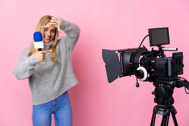 Женщина репортера держа микрофон и сообщая новости над изолированной розовой стеной фокусируя сторону. обрамление символ