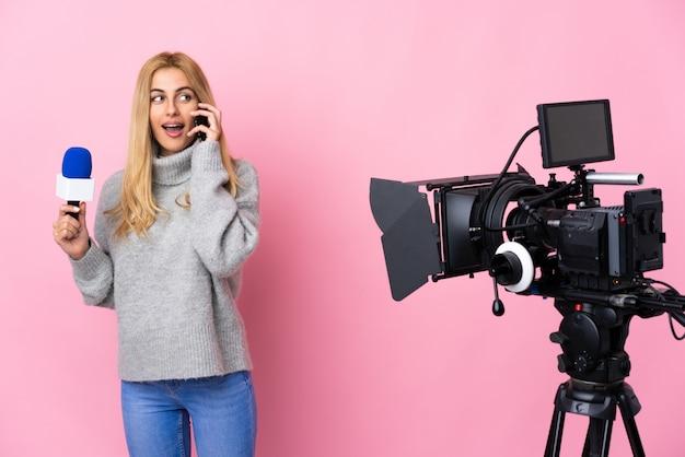 Репортер женщина, держащая микрофон и сообщения о новостях на изолированной розовой стене, сохраняя разговор с мобильным телефоном