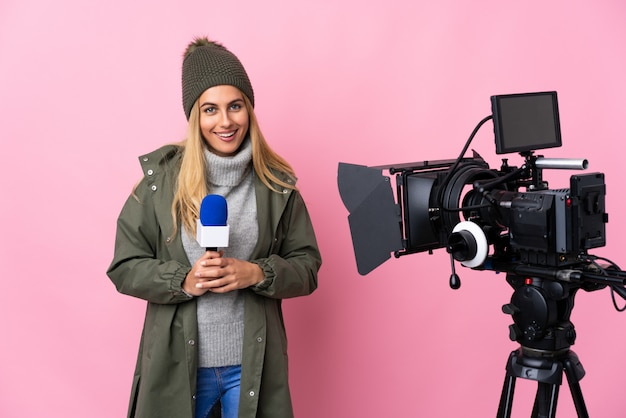 Репортер женщина, держащая микрофон и сообщения о новостях за изолированные розовые стены