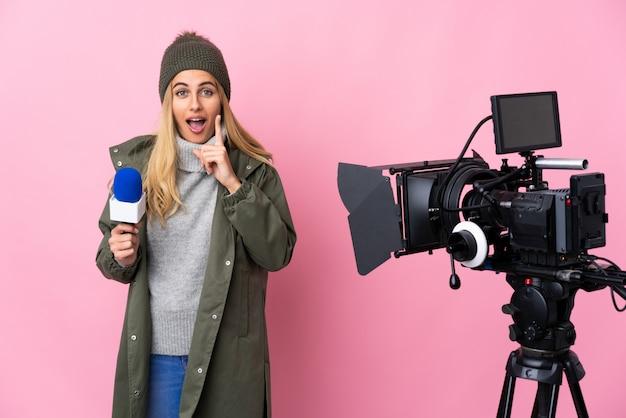 Репортер женщина, держащая микрофон и сообщения о новостях на изолированной розовой стене, намереваясь реализовать решение, поднимая палец вверх