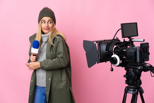 Репортер женщина, держащая микрофон и сообщения о новостях на изолированной розовой стене, делая сомнения жест, поднимая плечи