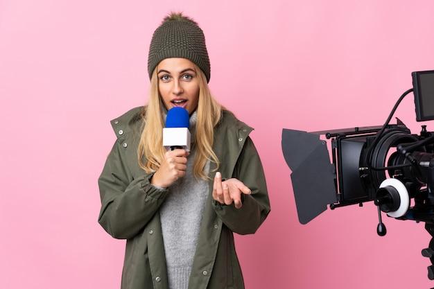 Репортер женщина, держащая микрофон и сообщения о новостях на изолированной розовой стене