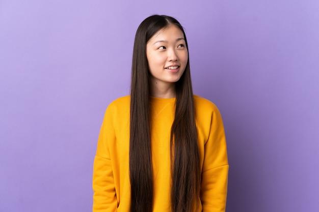 Молодая китайская девушка над изолированной фиолетовой стеной думая идея пока смотрящ вверх